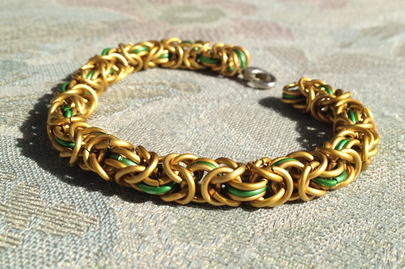 A chainmail bracelet I made from gold and green galvanized aluminium rings in byzantine weave.
